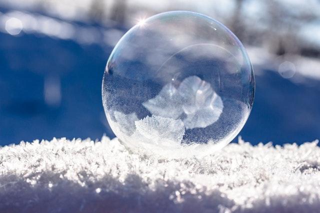 Jiskřivá námraza s mrznoucí bublinou, v pozadí modrá vodní hladina